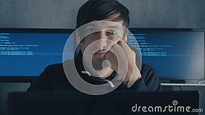 Desarrollador informático y hacker cansado está trabajando tarde en la noche en su computadora y sintiéndose sobrecargado de trab metrajes
