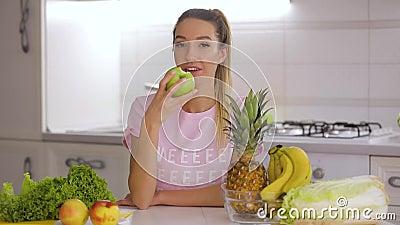 Desayuno sano, mujer sonriente feliz que come la manzana fresca verde en cocina almacen de metraje de vídeo