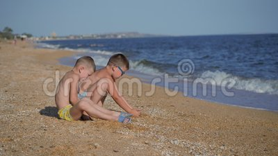 Descanse no mar com crianças Os meninos vomitam uma concha com areia As emoções das crianças Garotos jogam areia video estoque