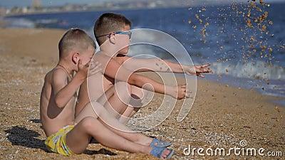 Descanse no mar com crianças Os meninos vomitam uma concha com areia As emoções das crianças Garotos jogam areia vídeos de arquivo