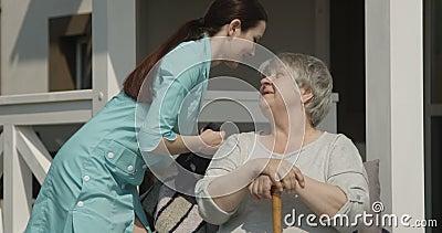 Descanso da fixação da enfermeira dos cuidados médicos que fluffing ao ar livre feliz de sorriso paciente da mulher adulta em Sun filme