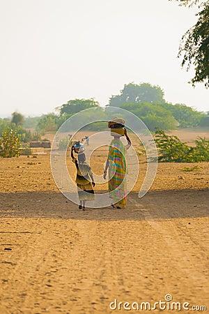 Descendant de mère cherchant des cruches d eau bien Image stock éditorial