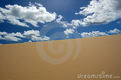 Desert dune and white clouds