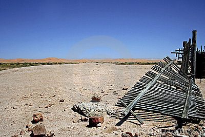 Desert landscape with broken wooden picket fence