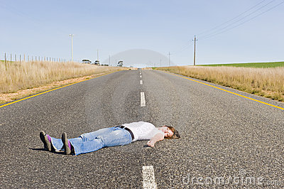 Deserted country-road with girl lying in the middl