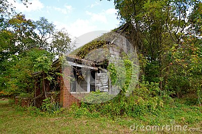 Deserted House Hidden in the Bushes Stock Photo