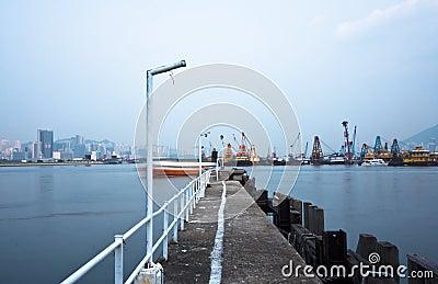 Deserted jetty at a foggy sea near a dutch city.