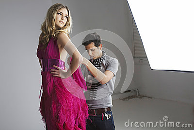 Designer adjusting dress on fashion model in studio