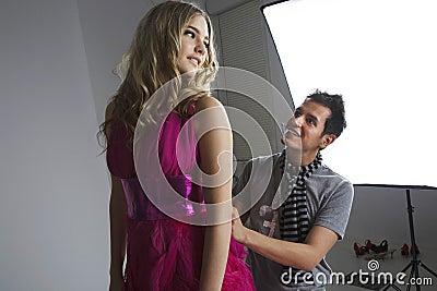 Designer adjusting fashion model s dress in studio