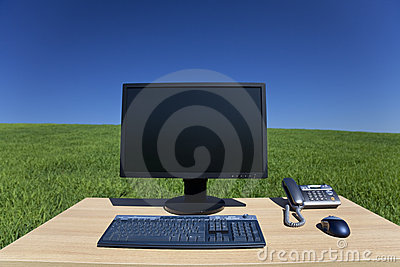 Desk and Computer In Green Field