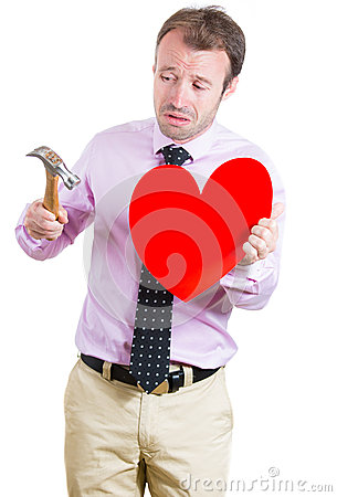 Desperate,sad, and looking crazy, holding a hammer and a heart in his hands