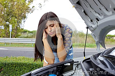 Desperate woman looking at broken engine