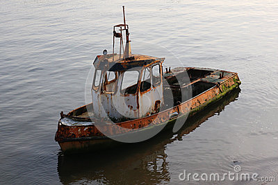 Destroyed, rusty, old boat in the water