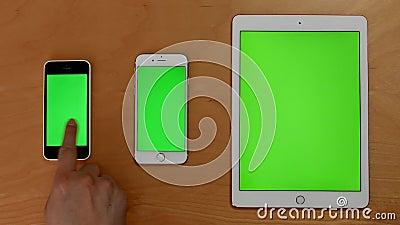 Det bästa skottet av handhandlaget ringer och ipad på den gröna skärmen