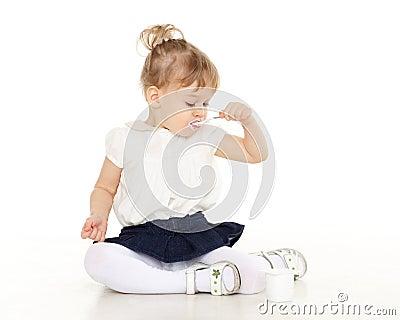 Det lilla barnet äter yoghurt