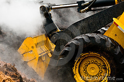 Detail loader and piles of steaming mulch