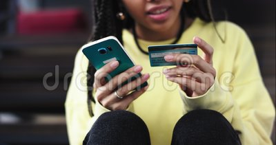 Details closeup african lady order something from her smartphone using a bank card she very careful typing her bank. Details , she sitting down on the modem stock video footage