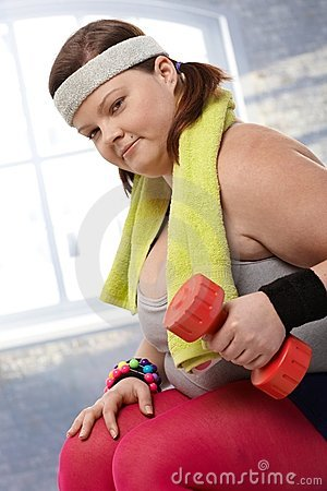 Determined fat woman with dumbbells