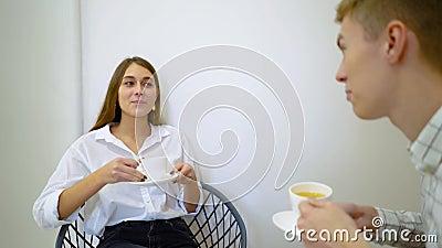 Deux étudiants féminins de lycée parlant tenant des boissons se reposant sur un sofa dans le salon clips vidéos