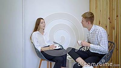 Deux étudiants féminins de lycée parlant tenant des boissons se reposant sur un sofa dans le salon banque de vidéos