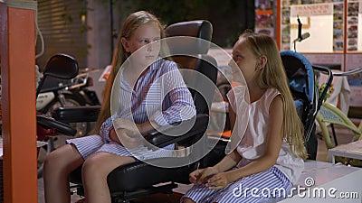 Deux amies qui parlent d'extérieur Une joyeuse adolescente racontant des histoires en soirée sur une rencontre en plein air clips vidéos