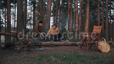 Deux amis masculins s'asseyant sur des bois d'identifiez-vous, faisant cuire le barbecue et parler clips vidéos