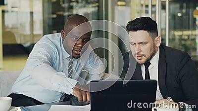 Deux collègues d'affaires regardant l'ordinateur portable et discutant leurs projets dans le bureau moderne avec des murs de verr clips vidéos