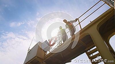 Deux dockers, collègues et colleages regardent l'appareil-photo et remettent l'ondulation à un port industriel banque de vidéos