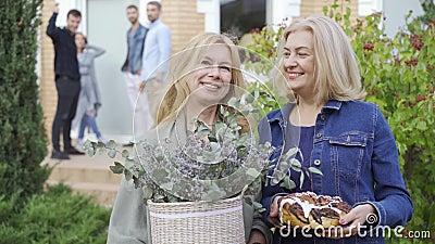 Deux femmes adultes caucasiennes sourient et tiennent un gâteau et un seau de fleurs Compagnie sur le porche en arrière-plan banque de vidéos