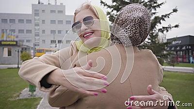 Deux femmes caucasiennes matures en vêtements élégants et lunettes de soleil se rencontrent après le voyage Des amies qui se serr banque de vidéos
