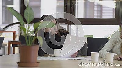 Deux filles attirantes s'asseyant à la table ont étayé des têtes avec des mains dans le bureau, discutant le nouveau projet Les f banque de vidéos