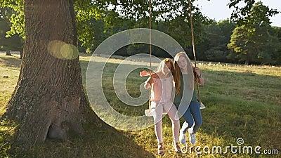 Deux filles heureuses qui balancent la corde à l'extérieur - ralenti clips vidéos