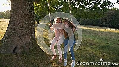 Deux filles heureuses sur la corde swing - slow mo banque de vidéos