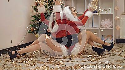 Deux filles jetant les confettis en l'air d'or en partie de nouvelle année dans 4K banque de vidéos