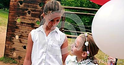 Deux filles souriant tandis que se tenir monte en ballon en parc banque de vidéos