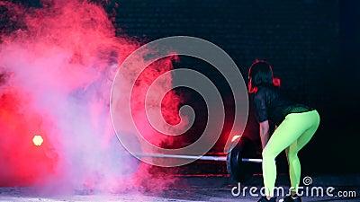 Deux filles sportives dans les paires faisant la diverse force s'exerce avec un barbell, la nuit, à la lumière de multicolore clips vidéos