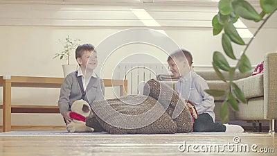 Deux garçons jouant les jouets et les coussins bourrés banque de vidéos