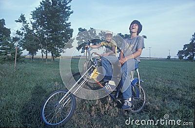 Deux garçons s asseyant sur leurs vélos Photo éditorial