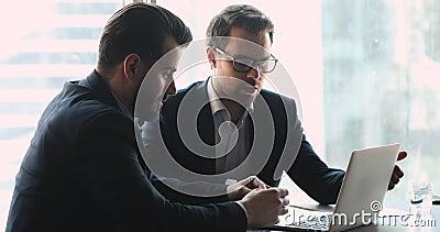 Deux hommes d'affaires concentrés regardant la présentation sur un ordinateur portable au bureau banque de vidéos