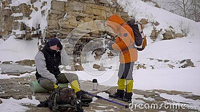Deux randonneurs cessés sur la berge pour avoir un repos et pour boire du thé chaud pendant la hausse d'hiver banque de vidéos