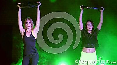 Deux sportifs, beau, des femmes faisant la force s'exerce avec les plats lourds, la nuit, dans la fumée légère, brouillard, dedan clips vidéos