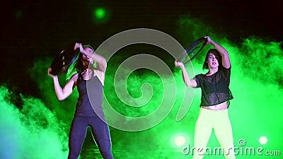 Deux sportifs, beau, des femmes faisant la force s'exerce avec les plats lourds, la nuit, dans la fumée légère, brouillard, dedan banque de vidéos