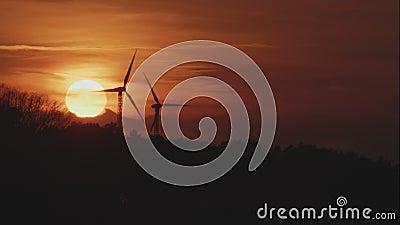 Deux turbines de vent tournantes derrière Forest At Sunset banque de vidéos