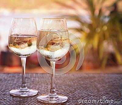 Deux verres de vin blanc avec de la glace sur une table au for Position des verres sur une table