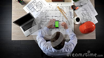 Developer checking information about house construction on green screen phone Stock Photo