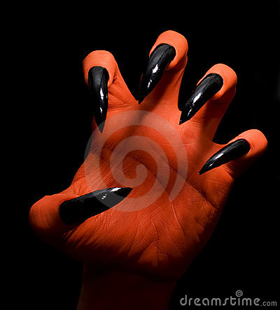 Red spooky devil hand on a dark background catching you.