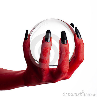 Devil s hand holding crystal ball.
