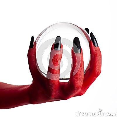 Devil s hand holding crystal ball.
