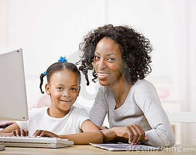 Devoted mother helping daughter do homework