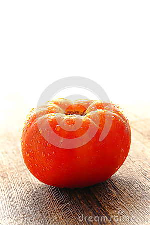 Dew on Organic Red Beefsteak Tomato on Wood Table